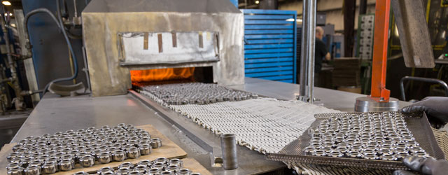 Pressed metal parts being placed into oven for heat treat an sintering